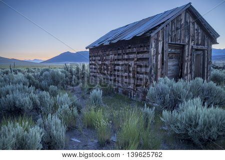 Old building at sunrise surrounded by sagebrush and rabbit grass.