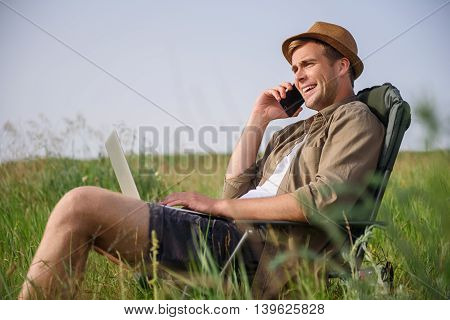Carefree young man is resting on meadow in vacation. He is sitting on folding chair and carrying computer. Man is talking on phone and laughing