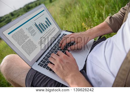 Close up of male hands typing on computer. Man is sitting in meadow