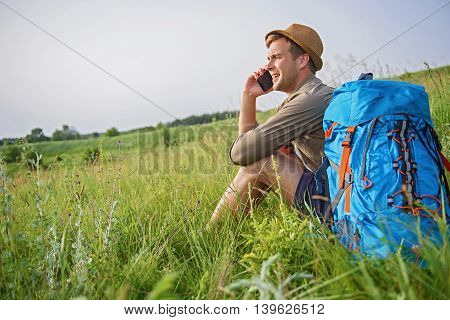 Joyful young man is talking on mobile phone and smiling. He is sitting on grass near touristic backpack