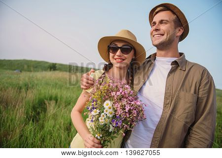 Cheerful lovers are dating in nature. They are standing in meadow and embracing. Woman is holding bouquet