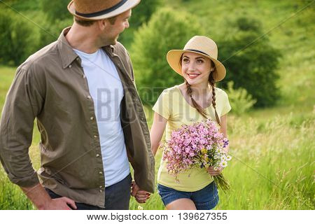 Joyful loving couple having date in meadow. They are holding hands and smiling. Woman is carrying flowers