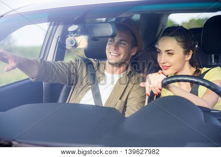 Carefree loving couple making journey together. Woman is sitting and driving a car. Man is pointing finger forward and smiling