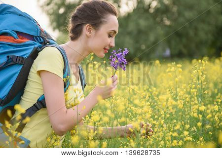 Cheerful female tourist is enjoying nature on field. She is smelling flower and smiling. Woman is standing with backpack