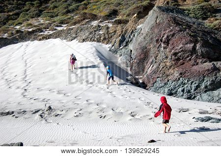 kids running up the white sand dunes at Julia Pfeiffer State Beach. Big Sur, California