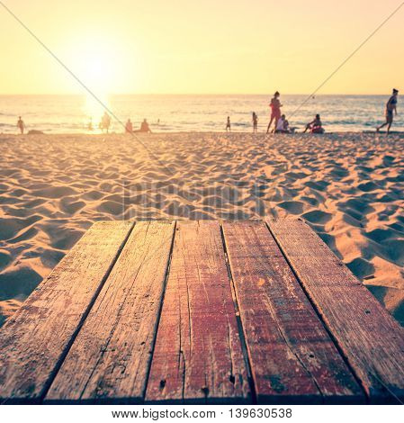 Top Of Wooden Table At Sunset Beach With Lens Flare. Warm Toning Effect. Retro And Vintage Style