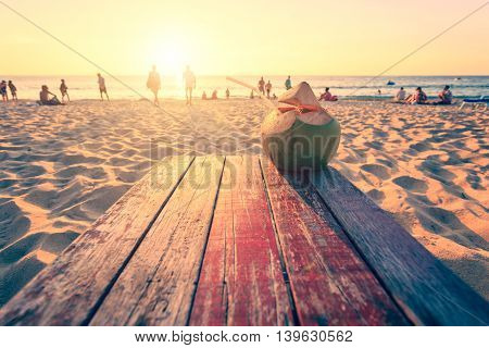 Coconut On Top Of Wooden Table At Sunset Beach In Thailand With Lens Flare. Warm Toning Effect. Retr