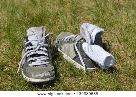 Little boy shoes, gray, with socks stuck inside on the grass