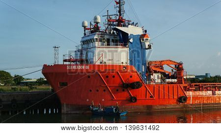 Vung Tau, Vietnam, 30th June 2016. Offshore Supply Ship 'Sea Meadow 08' maintained in Harbor. Red Vessel Painted by Workers. Red Painting Refreshed.