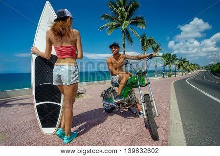 Boy and girl surfers having fun with surfboards on the road