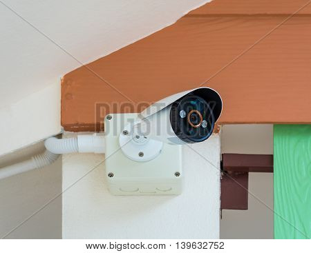 Close-up of CCTV security camera under roof of the house