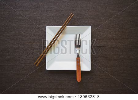 Empty white plate with fork and  chopsticks wooden table