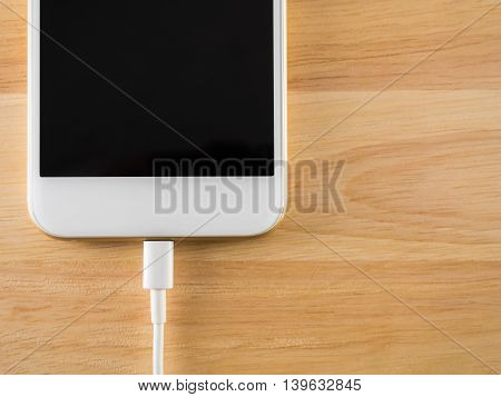 Top view (Flat Lay) of smart phone charging with USB cable on wooden texture background Copy space