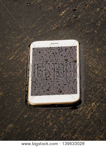 Damage and wet smart phone dropped on flooding floor with water drop on screen after the rain