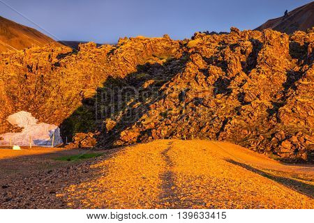Fairy dawn. Early morning in the Arctic. Sunrise National Park Landmannalaugar, Iceland. Valleys, mountains and glaciers covered with warm orange light