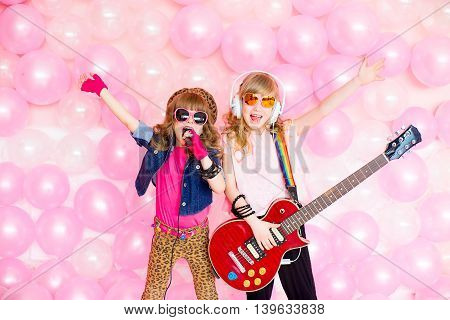 two little girl singing a song with a microphone and a guitar on a background of pink balloons