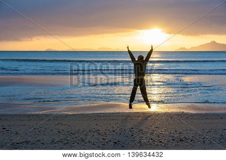Sunrise glistens over water from horizon and off-shore islands as boy star jumps with happiness on wintry morning at waters edge on beach Waipu Cove New Zealand