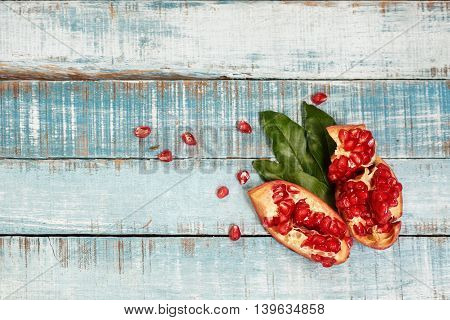 Sweet ripe sliced pomegranate on blue wood with leaves and seeds. Flat lay. Healthy eating background text space.