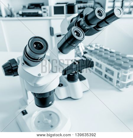 Science microscope on lab bench. Microbiology laboratory. Blue toned image of binocular microscope