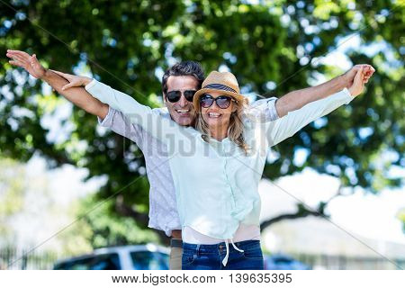 Cheerful couple with arms outstretched standing on street in city