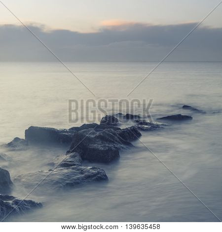 Peaceful Cross Processed Landscape Image Of Calm Sea Over Rocks At Dawn