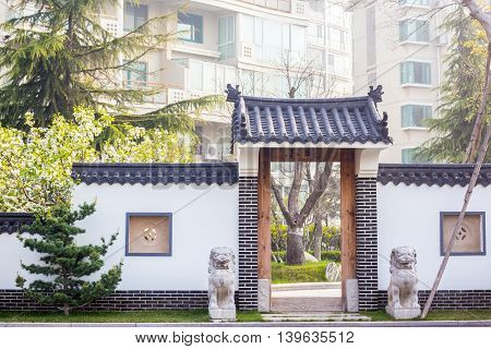 Qingdao China 04/22/2016 Traditional Chinese gate with two stone lions on each side leading to a living area in Qingdao China