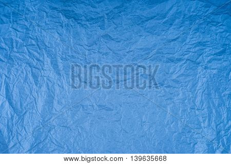 Background of blue empty wrinkled paper. Backdrop texture with copyspace and rough rumple surface.