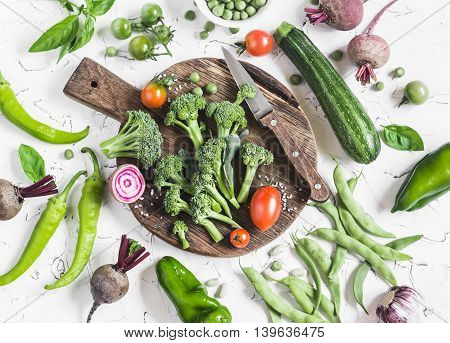 Fresh vegetables - broccoli zucchini peppers beets green beans and peas tomatoes on a light background. Raw ingredients for cooking. Top view