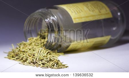 Rosemary cooking spice spilling out from the jar