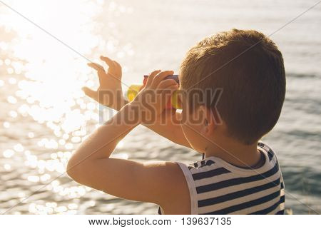 little boy looks into the distance through binoculars and touches his hand glare on the water