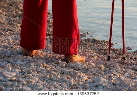 human legs in red pants with Nordic walking poles in the background of the sea