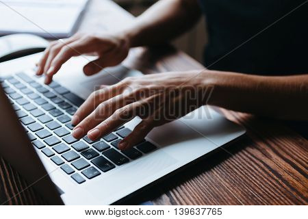 Female hand writing something on the laptop keyboard