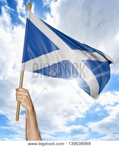 Person's hand holding the Scottish national flag and waving it in the sky, 3D rendering