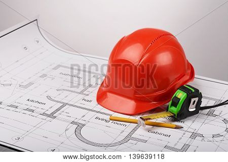 Construction helmet and a tape measure, carpenter's pencil, construction of the building layout, building drawing on paper, protective clothing