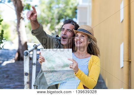 Cheerful couple with map standing on walkway in city