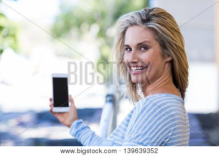 Portrait of cheerful woman holding smartphone at street in city