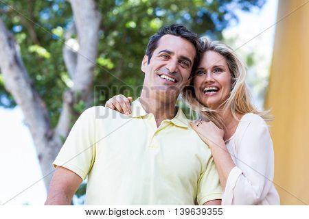 Low angle view of happy couple standing against tree