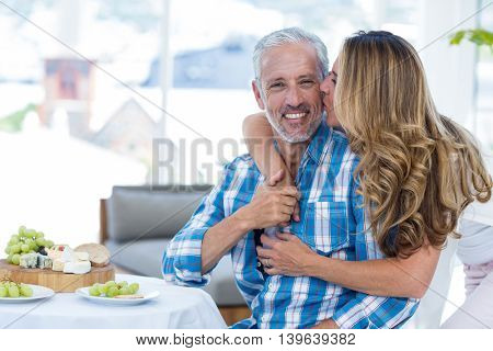 Woman kissing husband by table in restaurant