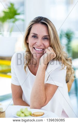 Portrait of beautiful woman with hand on chin at table in restaurant