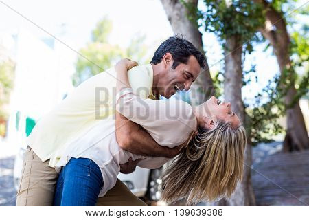 Side view of cheerful couple embracing on street in city