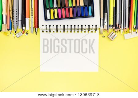 Bright Office And School Stationary With Notepad On Yellow Writing Desk Background