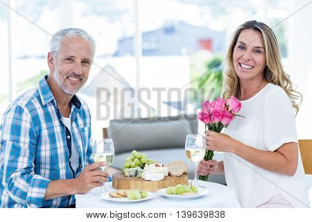 Portrait of smiling woman holding pink roses while having food with husband in restaurant