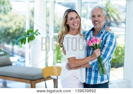 Portrait of happy mature couple embracing while standing in restaurant