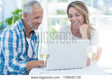 Happy mature couple using laptop at table in restaurant