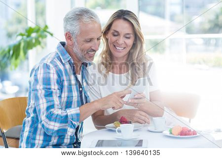 Happy mature couple looking in cellphone while sitting by table in restaurant