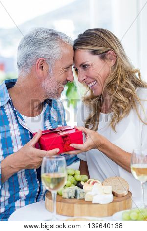 Romantic mature couple holding gift while sitting by table in restaurant