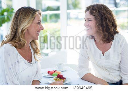 Happy female friends having food in restaurant