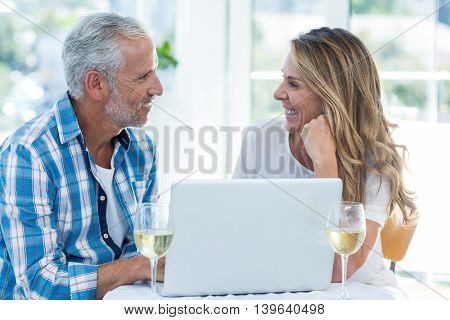Cheerful mature couple talking while sitting by table in restaurant