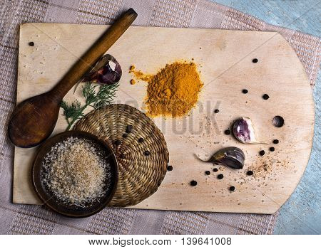 A wooden board with garlic, pepper, salt and spices