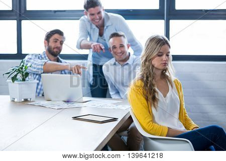 Depressed businesswoman sitting while colleagues laughing on her in creative office